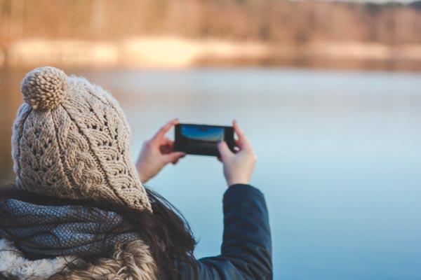 Foto per riparazione smartphone. Nella foto una ragazza ritrae un lago