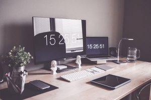 Foto in stile vintage di una scrivania con tre monitor pc e mac in bella vista
