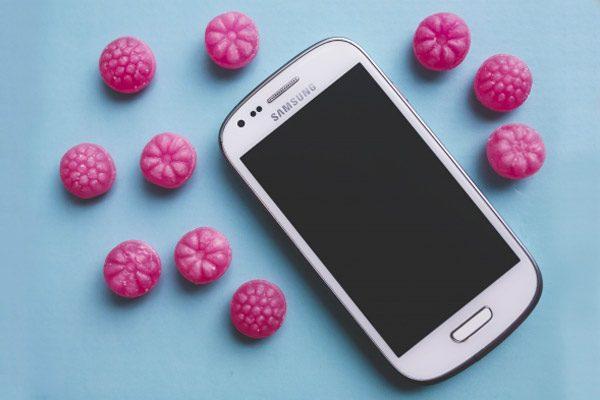 In foto un telefono per la riparazione samsung. Foto con colori pastello e carammelle fucsia