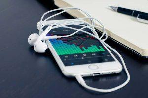 Foto iPhone 6s con cuffie e applicazione aperta con della musica