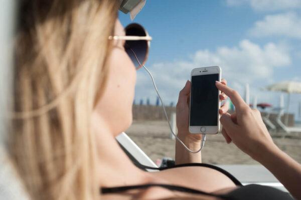 Modella usa Instagram sul lettino mentre carica con Holy Plug