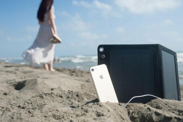 Holy Plug sulla riva del mare con iPhone in carica